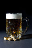 Mug of Fresh Beer with Foam and Peanut in Shell Isolated on Black Royalty Free Stock Photography