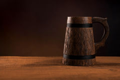 Mug of fresh beer on a wooden table. Standing on a wooden table on a dark red background Royalty Free Stock Photos