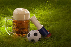 Mug of fresh lager, vuvuzela and small soccer ball on the grass. Stock Photography