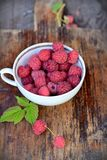 Mug with fresh raspberries. Raspberries in small mug on old wooden Royalty Free Stock Image