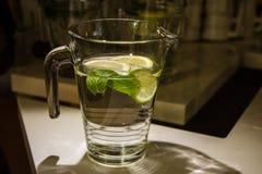 A mug of fresh water with lemon. A big mug of fresh transparent water with lemon and mint leaves Royalty Free Stock Photography