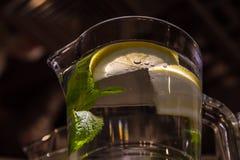 A mug of fresh water with lemon. A big mug of fresh transparent water with lemon and mint leaves Stock Image
