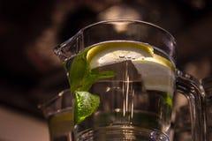 A mug of fresh water with lemon. A big mug of fresh transparent water with lemon and mint leaves Stock Photos
