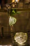 A mug of fresh water with lemon. A big mug of fresh transparent water with lemon and mint leaves Royalty Free Stock Image