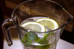 A mug of fresh water with lemon. A big mug of fresh transparent water with lemon and mint leaves Royalty Free Stock Photos