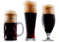 Mug of frosty dark beer with foam. Isolated on a white background Royalty Free Stock Photography