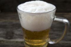 Beer. Mug with a frothy beer close-up on a wooden background Royalty Free Stock Photography