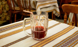 Mug of fruit drink. Close-up of a half-empty mug of fruit drink on a stripy cloth Stock Images