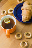 Mug full of black tea with lemon,  croissant on plate and small bagels Stock Images