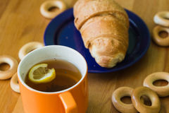 Mug full of black tea with lemon,  croissant on plate and small bagels Royalty Free Stock Photography