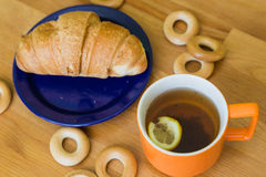 Mug full of black tea with lemon,  croissant on plate and small bagels Stock Image