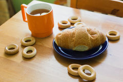 Mug full of black tea with lemon,  croissant on plate and small bagels Royalty Free Stock Images