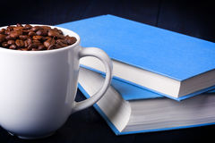 Mug full of coffee beans and two blue books Stock Photo