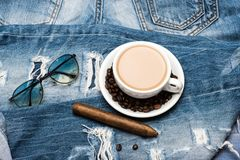 Mug full of coffee with milk, sunglasses and cigar on jeans. Daily ritual concept. Cup with coffee and beans on plate on Royalty Free Stock Images