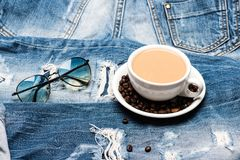 Mug full of coffee with milk and sunglasses on jeans, defocused. Coffee break concept. Cup with coffee and beans on Stock Image