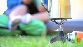 Mug on gas-burner and woman in a tent. Big metal travel mug stands on burning gas-burner with gas bottle on green grass at the background of woman sitting in a stock footage