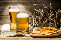 Mug, glass of beer with wheat spikelets and potato chips. Mug, glass of beer on linen cloth with wheat spikelets and potato chips Stock Photography