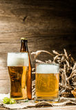 Mug, glasse, bottle of beer with foam on blank wooden background Stock Photos