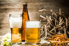 Mug, glasse, bottle of beer with foam on wooden table Stock Images