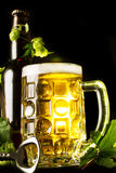 Mug of golden beer, bottle and openner with hop leaves Royalty Free Stock Image