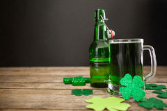 Mug of green beer, beer bottle and shamrocks for St Patricks Day Royalty Free Stock Photography