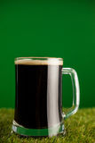 Mug of green beer on grass for St Patricks Day Stock Images