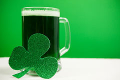 Mug of green beer and shamrock for St Patricks Day Stock Image