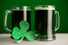 Mug of green beer and shamrock for St Patricks Day. Glass of green beer and shamrock for St Patricks Day against green background Royalty Free Stock Images