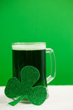 Mug of green beer and shamrock for St Patricks Day. Glass of green beer and shamrock for St Patricks Day against green background Stock Photos