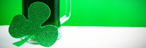 Mug of green beer and shamrock for St Patricks Day. Glass of green beer and shamrock for St Patricks Day against green background Stock Photo