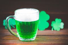 A mug of green beer on the table. Clover leaves. Chest of gold, coins pile. St.Patrick's Day. A mug of green beer on the table. Clover leaves. Chest of gold stock image