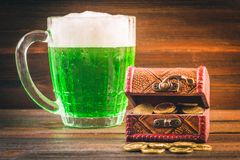 A mug of green beer on the table. Clover leaves. Chest of gold, coins pile. St.Patrick's Day. A mug of green beer on the table. Clover leaves. Chest of gold royalty free stock photography