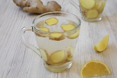 A mug of homemade ginger tea with lemon on white wooden surface stock photo