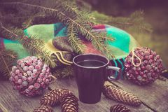 Mug of hot beverage on a rustic wooden table. Still life of cones, twine, packthread, fir branches. Preparing for Christmas. Stock Image