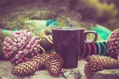 Mug of hot beverage on a rustic wooden table. Still life of cones, twine, packthread, fir branches. Preparing for Christmas. Stock Photography
