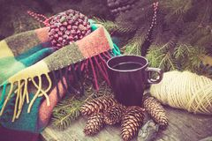 Mug of hot beverage on a rustic wooden table. Still life of cones, twine, packthread, fir branches. Preparing for Christmas. Stock Photo
