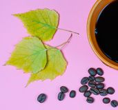 A mug of hot black coffee, dry fallen leaves, coffee beans on a colored background