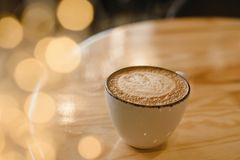 Mug of hot cappuccino on a wooden table in a cafe with yellow garland lights