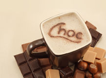 Mug of Hot Chocolate. Hot Chocolate in square mug with cocoa powder sprinkled on the frothy top to make the word choc with text area Stock Photography