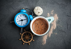 Mug of hot chocolate or cocoa. Breakfast concept, mug of hot chocolate or cocoa, alarm clock on concrete background Royalty Free Stock Photos