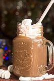 Mug of hot chocolate drink with marshmallow candies on top and l. Ights on Christmas tree and decorations stock photos