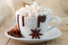 mug with hot chocolate, marshmallows and cinnamon on wooden table. Rustic style Royalty Free Stock Photo