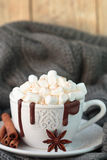 Mug with hot chocolate, marshmallows and cinnamon on wooden table. Rustic style Royalty Free Stock Images