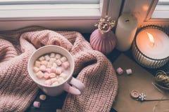 Mug of hot cocoa or hot chocolate with marshmallow on windowsill.  stock photo