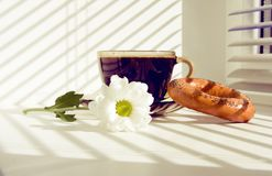 Mug of hot coffee and a flower on the windowsill Stock Images