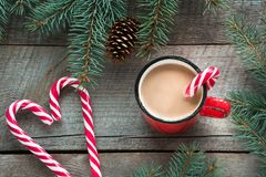 Mug hot coffee with milk, red candy cane in shape of heart on the wooden background. New Year. Holiday card. Rustic style. Top vie Stock Images