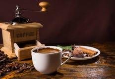 Mug of hot drink besides chocolate dessert Royalty Free Stock Images