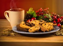 Mug with hot drink and Christmas cookies. Background with cup of chocolate, tea or coffee, festive decoration. Stock Photos