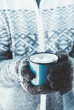 Mug with hot drink in male hands in winter. Closeup photo of tin mug with cocoa and marshmallows in male hands in mittens. Traveller in sweater drinking hot Stock Photos