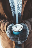 Mug with hot drink in male hands in winter. Closeup photo of tin mug with cocoa and marshmallows in male hands in mittens. Traveller in warm clothing drinking Stock Image